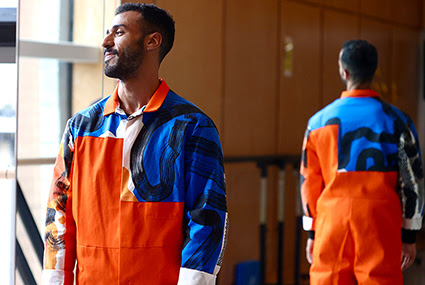 A photograph of a model wearing a jumpsuit with fabric designed by Zephir Liddell. The model is standing their back to a mirror in a dance studio, making the front and back of the jumpsuit visible. The jumpsuit is bright orange with a printed yoke and sleeves. The print is blue with abstract black lines.