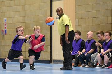 A group of young children with Dwarfism playing basketball