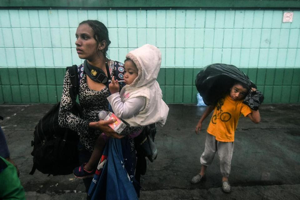 "An Honduran migrant woman and their children, who are taking part in a caravan towards the United States, are pictured at the ""Casa del Migrante"" (Migrant's House) in Guatemala City, on October 17, 2018. - A migrant caravan set out on October 13 from the impoverished, violence-plagued country and was headed north on the long journey through Guatemala and Mexico to the US border. President Donald Trump warned Honduras he will cut millions of dollars in aid if the group of about 2,000 migrants is allowed to reach the United States. (Photo by ORLANDO SIERRA / AFP)"