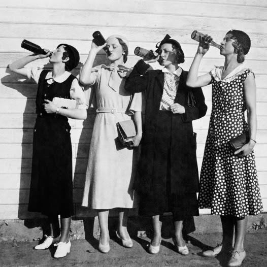 Flapper women drink in unison, ca. 1925.