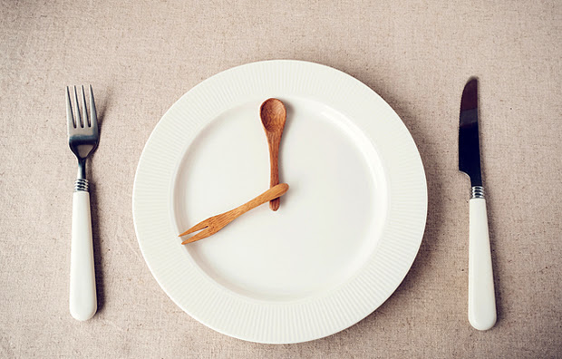 A plate with a knife and fork representing the hands of a clock.