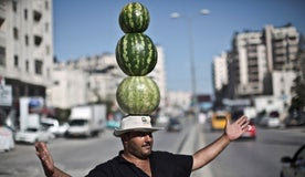 Palestinian fruit vendor Shaher Abu Yamin, 36, poses for a picture while balancing three watermelons on his head near the West Bank refugee camp of Kalandia, 2014.