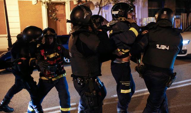 Agentes de la UIP detienen a un bombero durante los enfrentamientos tras la concetración por Gamonal en Madrid.