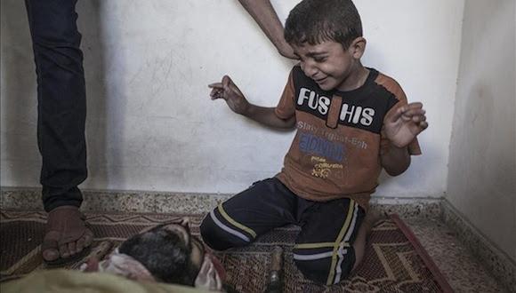 Foto: Un niño llora junto al cadáver de un familiar muerto en el ataque a la escuela de la ONU. Foto: Oliver Weiken/EPA.