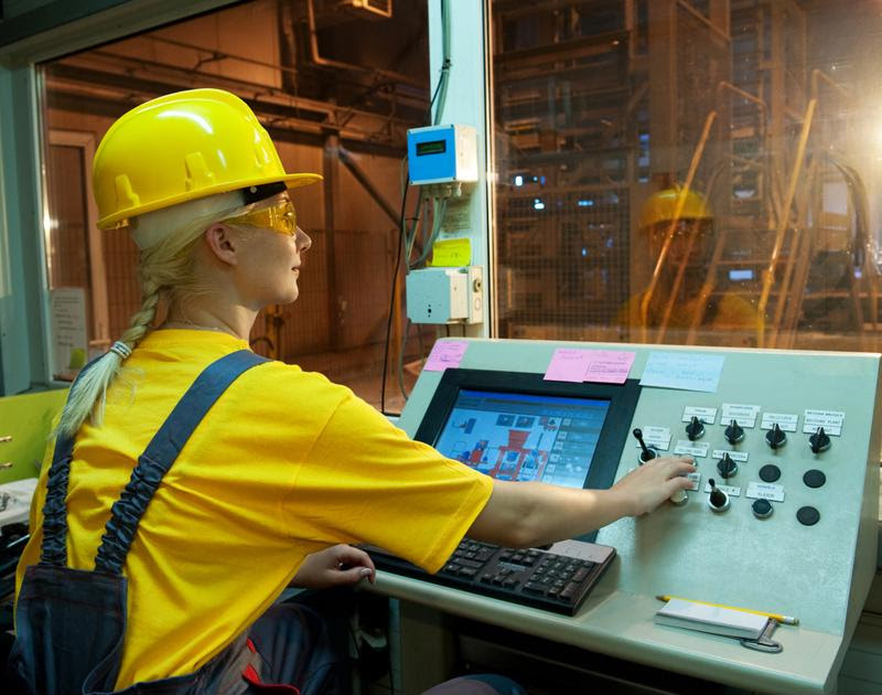 A factory worker at a control panel.