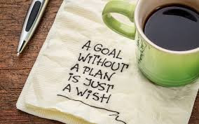 "A napkin with the words ""A goal without a plan is just a wish"", Sitting on the napkin is a cup of coffee and next to it is a pen"