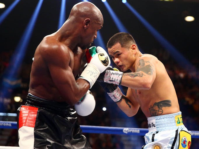 Marcos Maidana defends against Floyd Mayweather Jr. during their fight at MGM Grand.