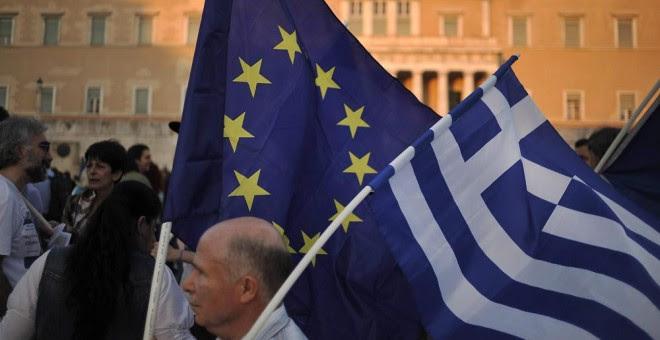 Un manifestante ondea una bandera de la Unión Europea y de Grecia durante una manifestación a favor de la zona euro en Atenas. EFE
