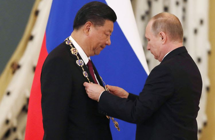 Vladimir Putin awards Chinese leader Xi Jinping the Order of St. Andrew the Apostle the First-Called during a ceremony at the Kremlin in Moscow yesterday. (Sergei Ilnitsky/AFP/Getty Images)</p>