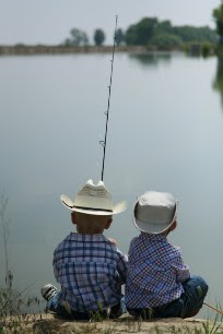Two young boys wearing cowboy hats, fishing, viewed from behind