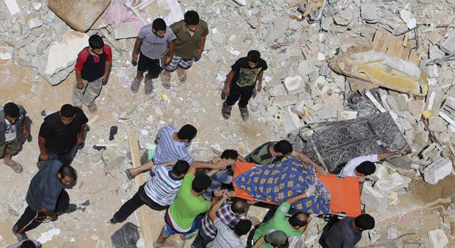 Palestinos trasladan el cuerpo de una mujer encontrado entre los escombros de una casa en Gaza.