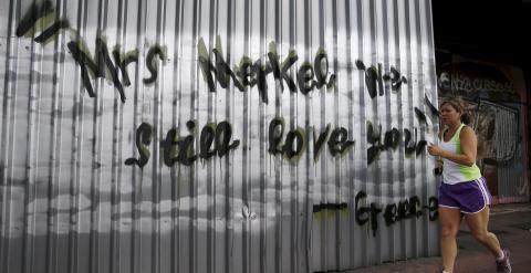 """Una mujer corriendo por las calles de Atenas, pasa junto a una pintada que, en inglés, dice """"Señora Merkel, todavía la queremos. Grecia"""". REUTERS/Alkis Konstantinidis"""