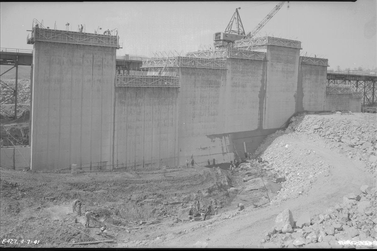 Black and white photograph of the Cherokee Dam construction site. The dam is partially built and surrounded by scaffolding. Workers can be seen on top of the dam, and on the ground.