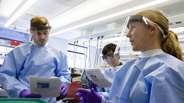 미셸시피 키오 (Michelle Cipicchio), 안면 보호막을 착용 한 실험실 기술자 2 명과 사진 촬영