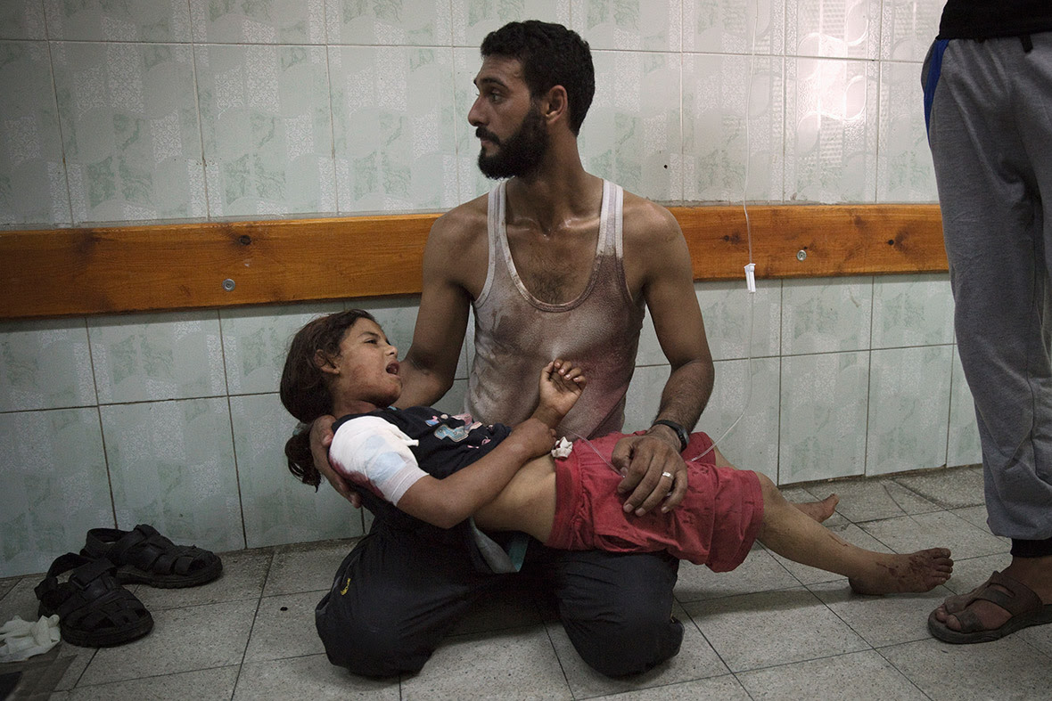 A man holds a girl, whom medics said was injured in the Israeli shelling of the school