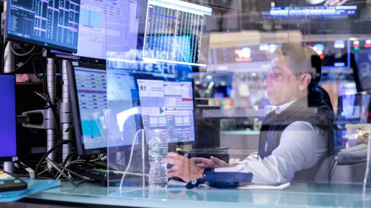A man sits at a computer with five monitors