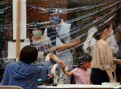 Los votantes usan cubrebocas mientras se preparan para emitir su voto en la elección de gobernador de Tokio.
