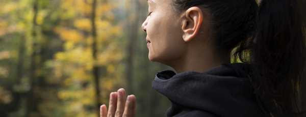 A woman praying in the forest with her eyes closed.