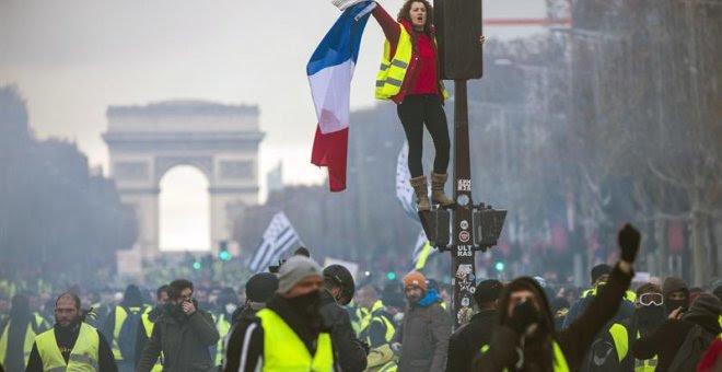 Una mujer grita consignas subida a un semáforo durante una protesta en los Campos Elíseos en París (Francia) hoy, 24 de noviembre de 2018. El ministro francés del Interior, Christophe Castaner, culpó hoy a la ultraderecha y a su líder, Marine Le Pen, de l