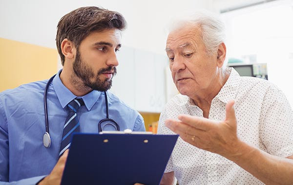 older male patient consulting his younger male doctor.