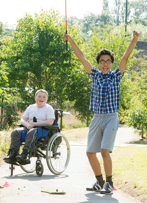 Two young men playing adapted golf outside