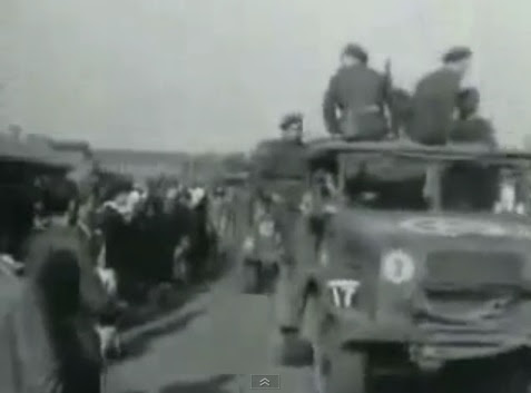 """American"" lorries with a                             five pointed star on the hood coming with                             German prisoners of war (1min. 49sec.)"