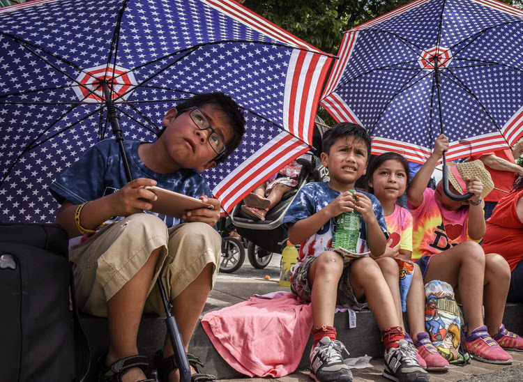 Daniel De la Torres, left, watches the National Independence Day with his cousins yesterday in Washington, DC. (Bill O'Leary/The Washington Post)</p>
