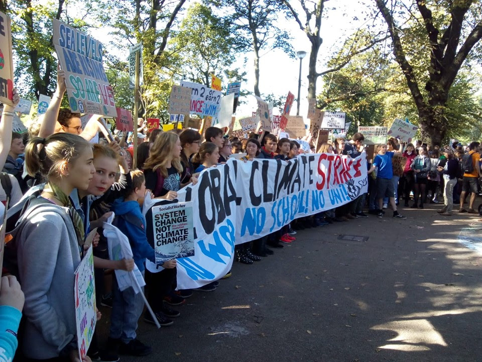 Schoolchildren at the front of a march holding a large, hand-painted banner which reads 'Global Climate Strike. No Work! No School! No Uni!'