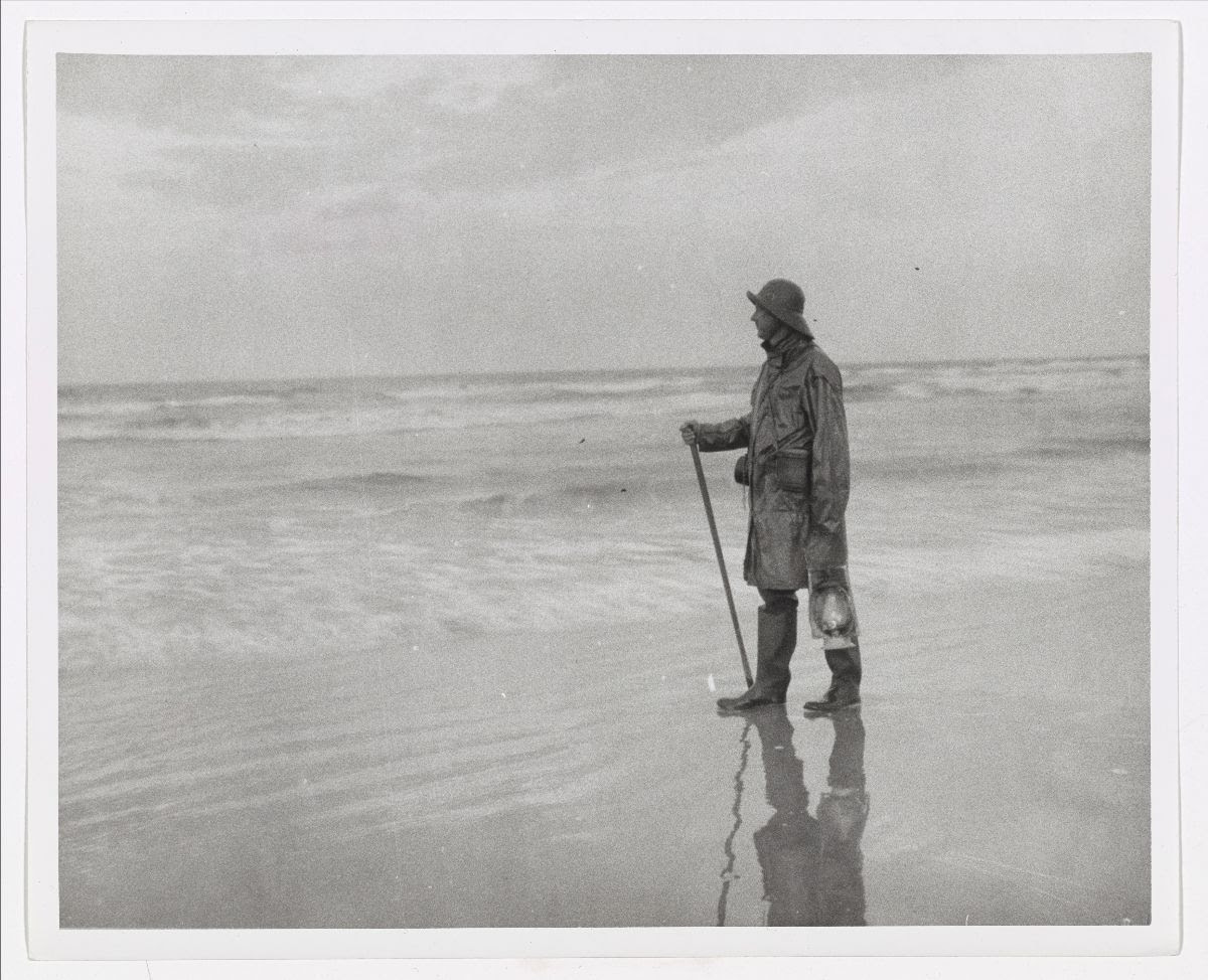 Black and white photograph of a coast guard member wearing a raincoat, hat, and boots, patrolling the beach.