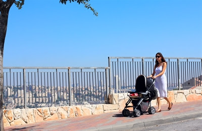 Mother strolls with infant in                 pram