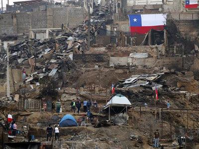 Voluntarios y residentes limpian escombros en una zona arrasada por el fuego en Valparaíso.