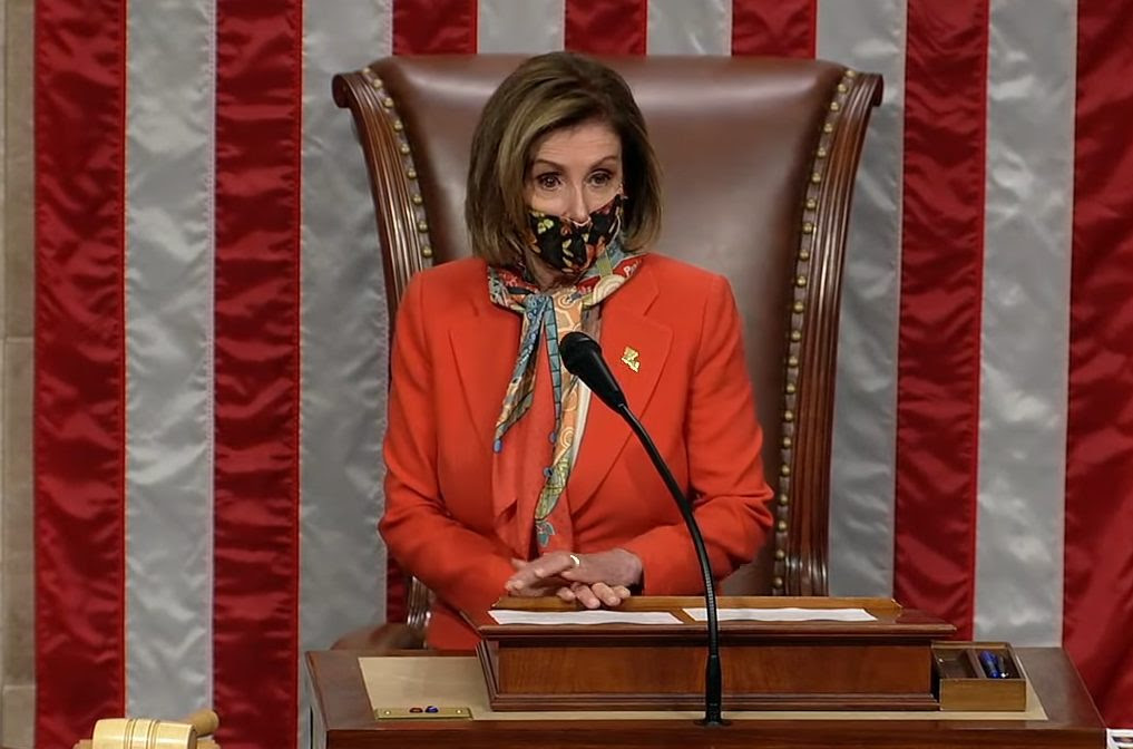 Nancy Pelosi stands behind a podium with an American flag behind her