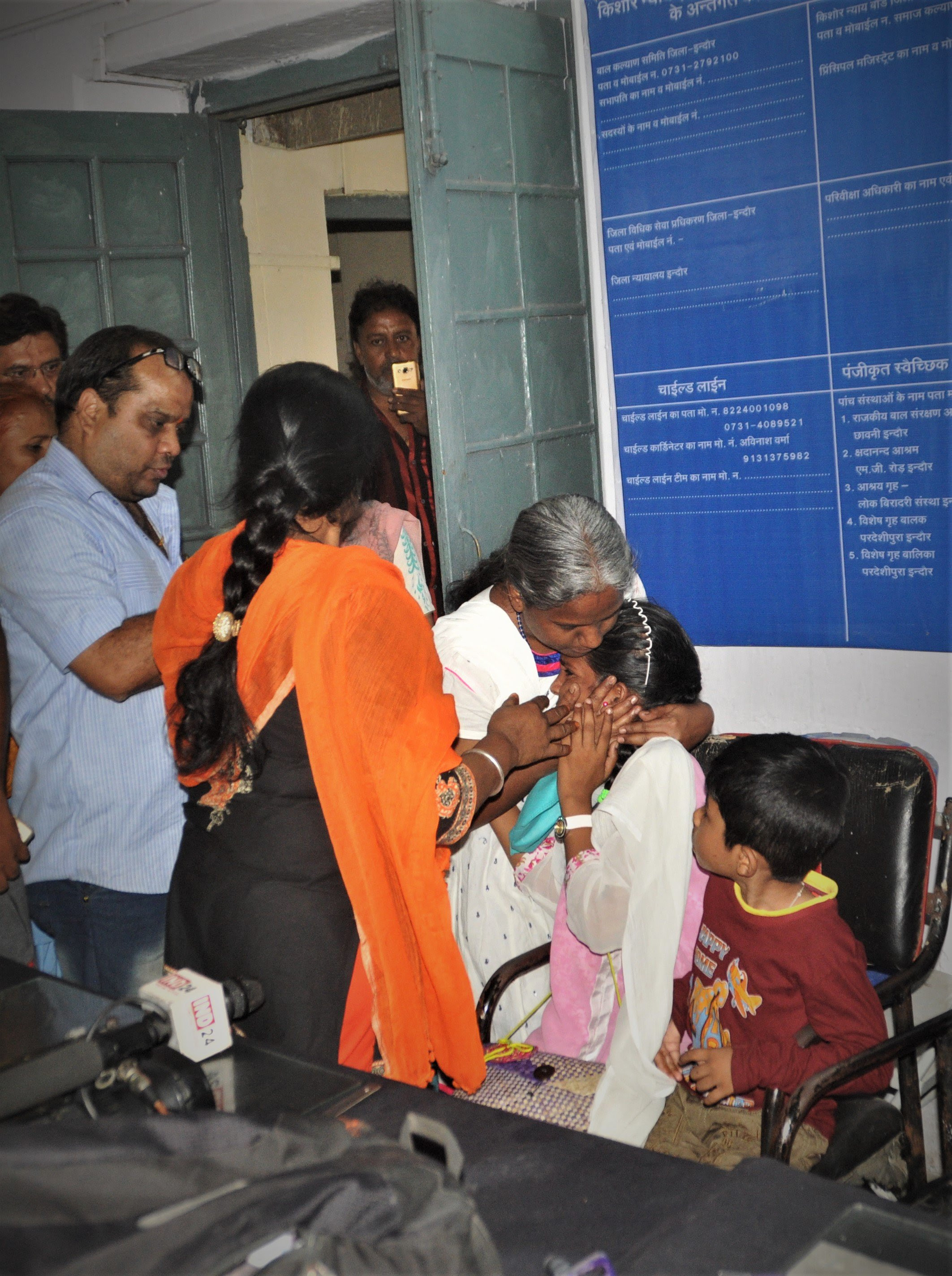 A mother tries to comfort her crying daughter, one of seven children detained at the railway police station in Indore, India, before they were separated. Hindu extremist group leader Vinod Mishra is in blue shirt. (Pawan Bhawar)