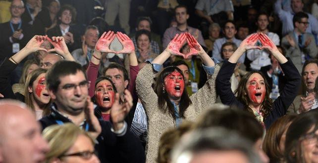 Cuatros mu8jeres con el rostro pintado de rojo gritan a favor del aborto durante el discurso de Rajoy en el Congreso del PP vasco en San Sebastián.