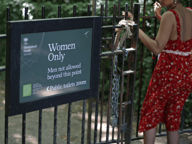 """The sign indicating the 'Women Only' swimming pool is seen attached to gates on Hampstead Heath in central London on June 27, 2018. - Can transgender women swim in the women's pond in Hampstead Heath's huge London park? The regulars are divided between the desire to preserve this """"sanctuary"""" and …"""