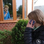 A young lady talks to an older lady on the phone through a window