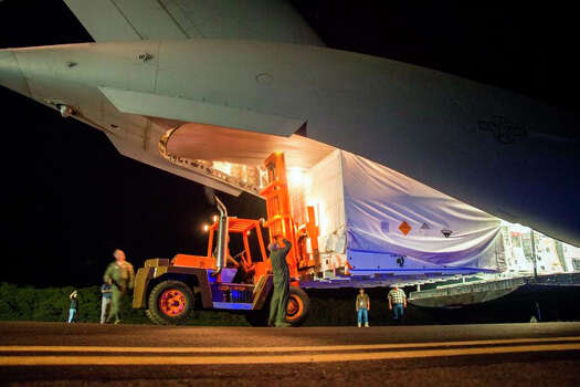 This April 17, 2014 image provided by NASA shows workmen unloading a saucer-shaped test vehicle for NASA's Low-Density Supersonic Decelerator (LDSD) project, at the U.S Navy's Pacific Missile Range Facility at Kekaha on the island of Kaua'i in Hawaii. The engineering test flight of this vehicle is scheduled for June 3, 2014. The saucer will be boosted to high altitudes via balloon and rocket, before releasing an inflatable doughnut-shaped tube and an enormous supersonic parachute -- possible landing technologies for future Mars missions.(AP Photo/NASA) Photo: HOPD / NASA