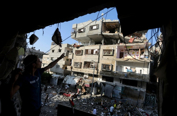 Palestinians inspect the rubble of a house after it was hit by an Israeli missile strike in Gaza City.