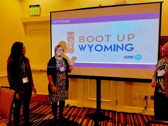 WDE staff look at Standards Supervisor Barb Marquer as she points to a screen she used for her presentation which features the logos for Boot Up Wyoming and the Wyoming Department of Education.