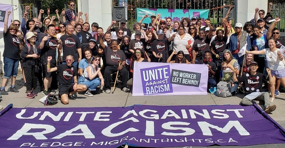 Close to 80 people wearing $15 & Fairness shirts pose behind a banner that reads Unite Against Racism