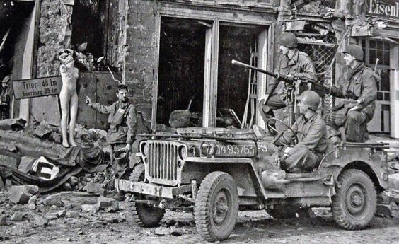 Already within German territory, GI ' s on your jeep, observe a mannequin with the German flag thrown on the floor, the end is near, 1945