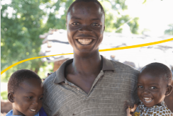 Shanu stands with his two children in Malawi
