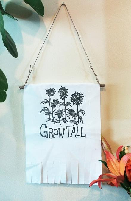 "Photo of a handmade wall hanging made out of muslin, a wooden hanger and black string. The hanging features a print of flowers with the words, Grow Tall,"" underneath."