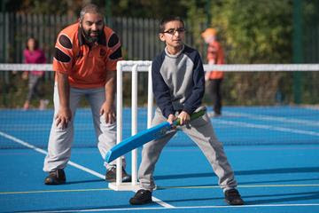 A young visually impaired boy playing adapted cricket with a coach behind him watching