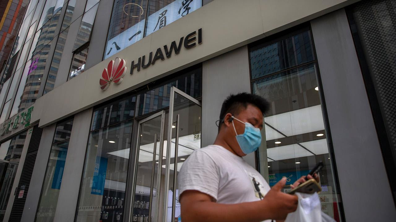 A man wearing a face mask looks at his smartphone as he walks past a Huawei store in Beijing.
