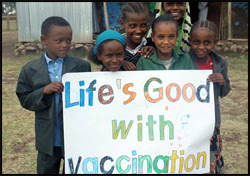 """The figure above is a photograph showing children holding a sign reading: """"Life's good with vaccination"""" in commemoration of CDC's 50 years of global immunization efforts."""