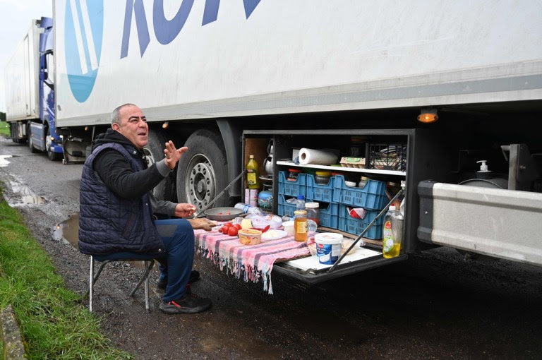 A Turkish long-haul truck driver eats his breakfast at a truck stop off the M20 motorway which leads to the Port of Dover, near Ashford in Kent, south east England on December 22, 2020, as he queues unable to continue his journey after France closed its borders to accompanied freight arriving from the UK due to the rapid spread of a more-infectious new coronavirus strain. - Britain sought to sound a note of calm saying they were working as fast as possible to unblock trade across the Channel after France shut its borders to UK hauliers in a bid to contain a new variant of the coronavirus. (Photo by JUSTIN TALLIS / AFP) (Photo by JUSTIN TALLIS/AFP via Getty Images)