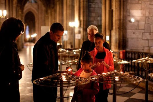 arack Obama and family lighting candle inside cathedral with pries