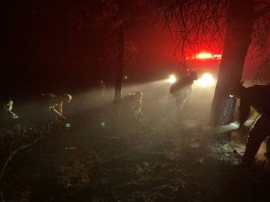Forest Rangers fight wildfire in smoky woods, a car's headlights lighing a path through the smoke