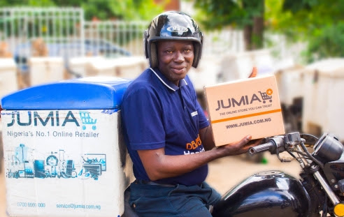 an holding a parcel while seated on a motorbike (© Jumia)